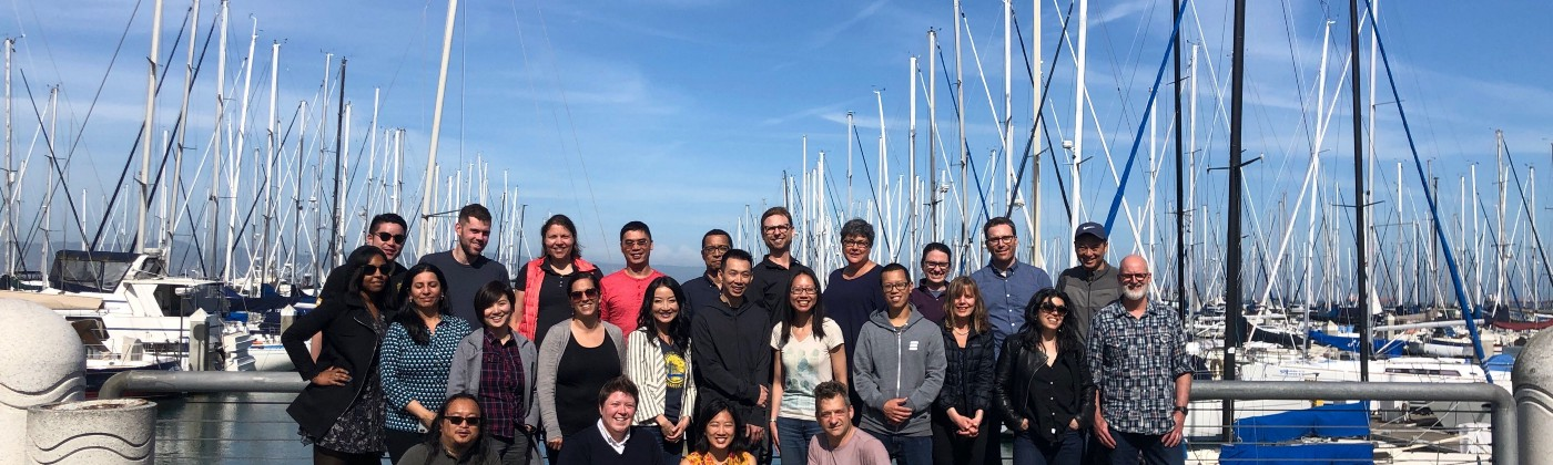 A picture of the Digital Services Team members smiling in the sun in front of some boats at the waterfront in San Francisco