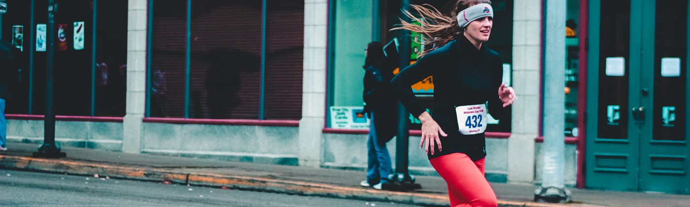 woman running in a race with red pants and a black shirt