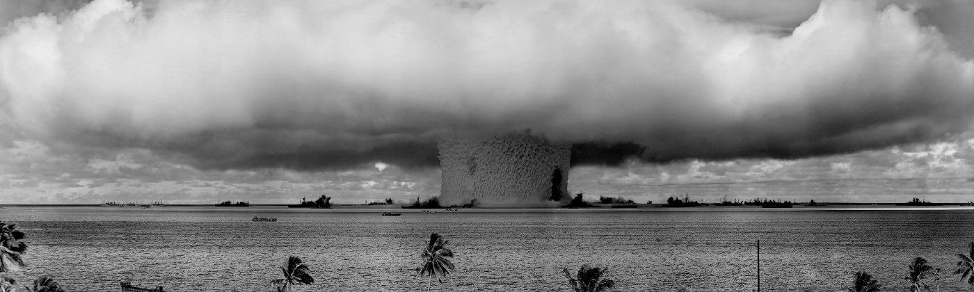 A grayscale image of a nuclear explosion off the coast of a beach.