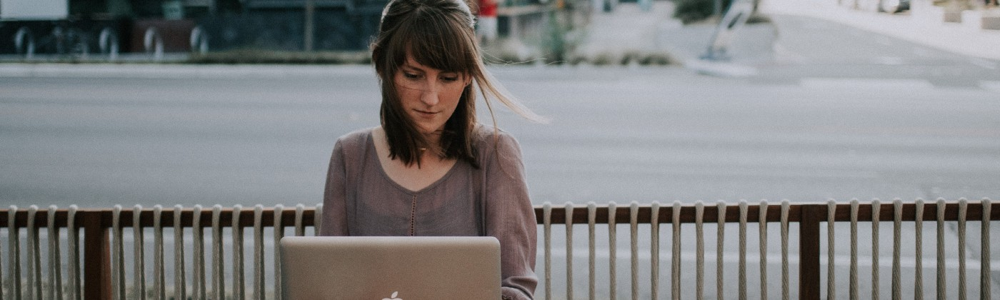 A women on her mac laptop facing the camera, sitting in a open patio cafe looking on to the intersection