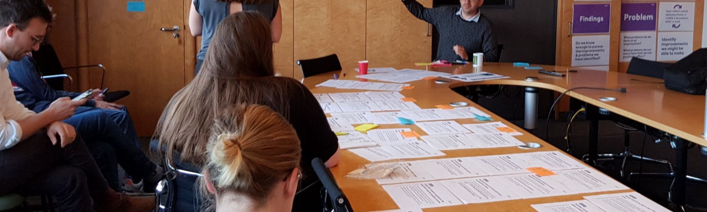 The team sit around a table with papers on as Tom Steinberg gestures to a wall of post it notes clustered together.