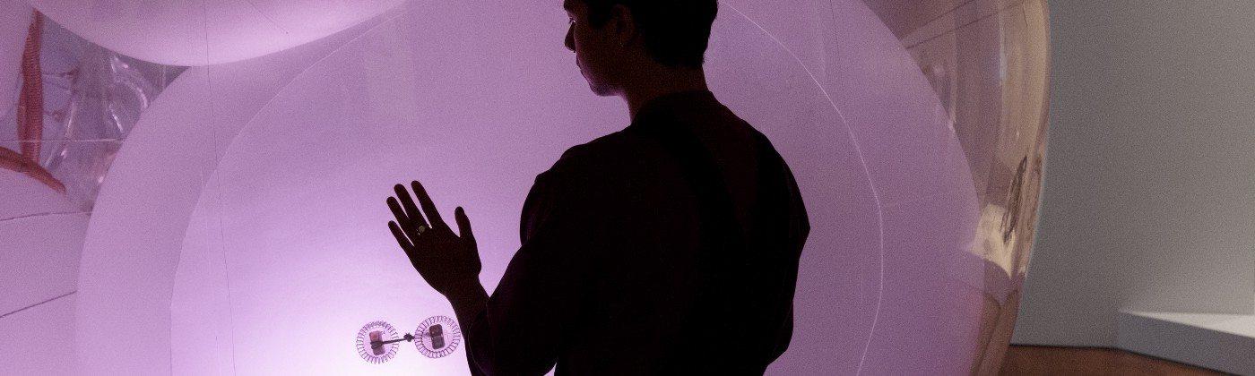 Silhouette of museum patron with one hand touching a giant, glowing pink orb.