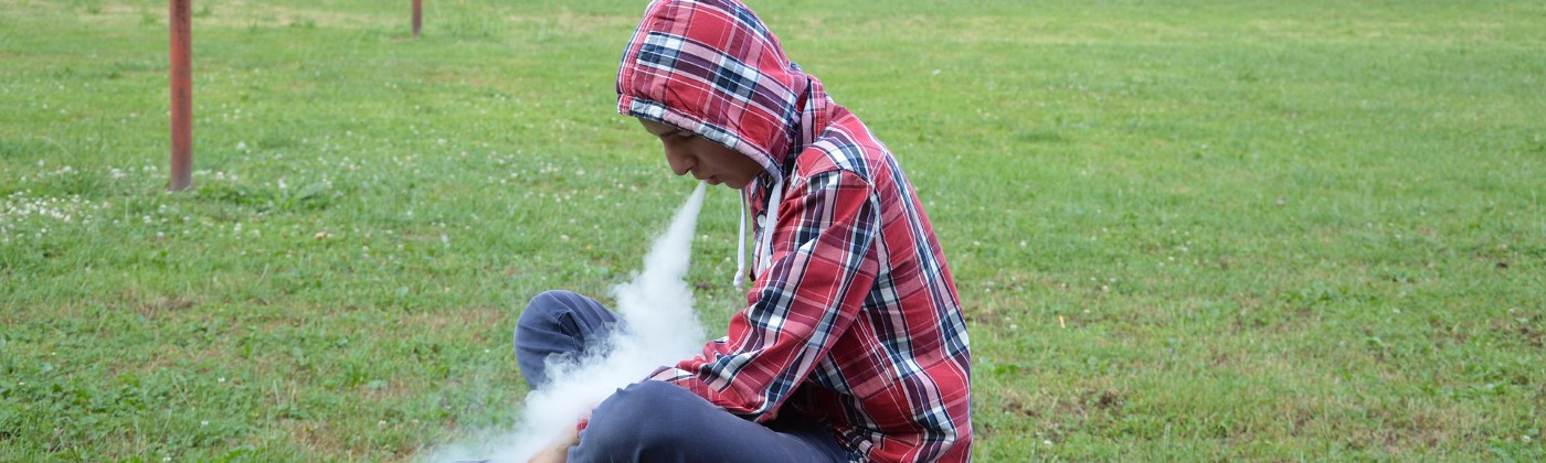 Young man vaping on a park bench.