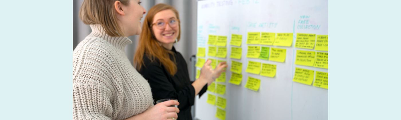 Two happy women discussing a whiteboard that is covered in sticky notes.