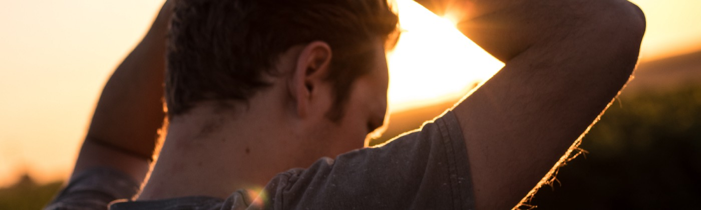 Man holding his hair against sunlight—Losing motivation is not the same as giving up