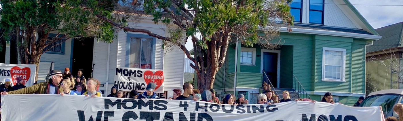 Demonstrators gather in front of the house on Magnolia Street. People of all ages hold banners supporting Moms 4 Housing.