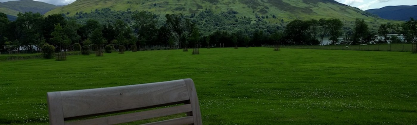 Sitting outside, feet up on a chair. Expansive lush grass and a gentle mountain in the background—Scotland