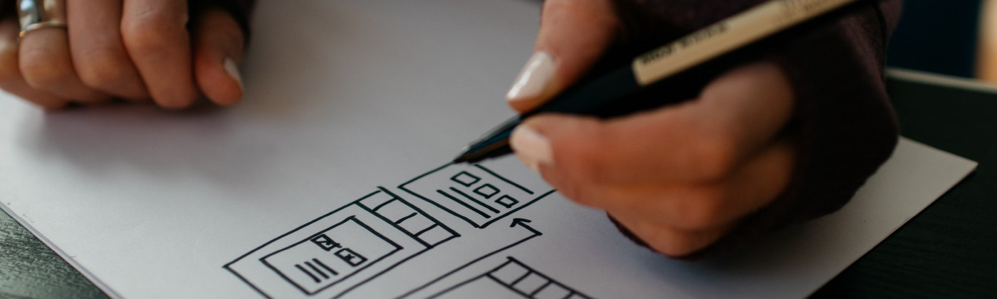 Closeup of a pair of hands sketching UI components on a sheet of paper