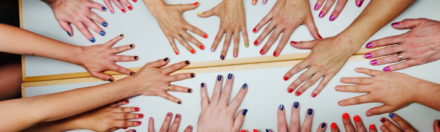 Picutre of a lots of hands on a table, showing of colorful nailpolish.