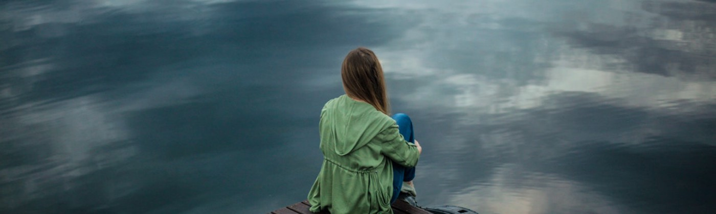 A woman sitting on the edge of a deck, over water, looking into the distance