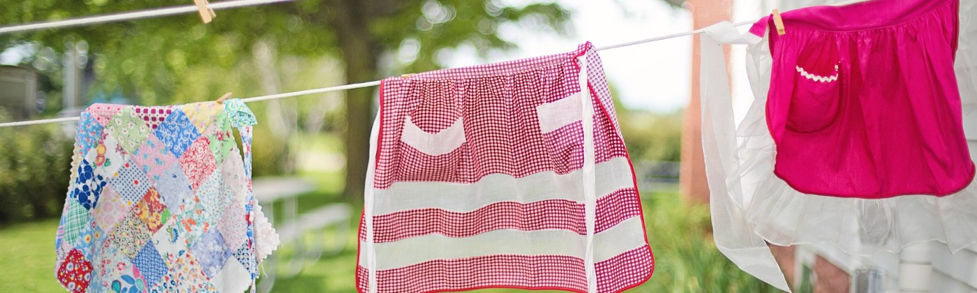Three colorful aprons on a clothesline in a sunny yard.