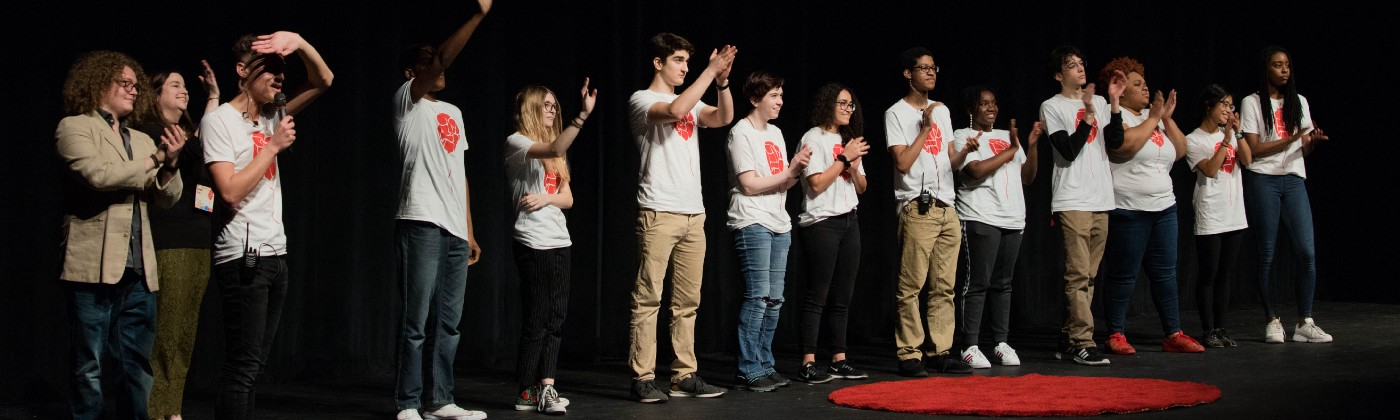 A group of young people, all wearing event-themed shirts, stands on a stage, claps, and smiles.