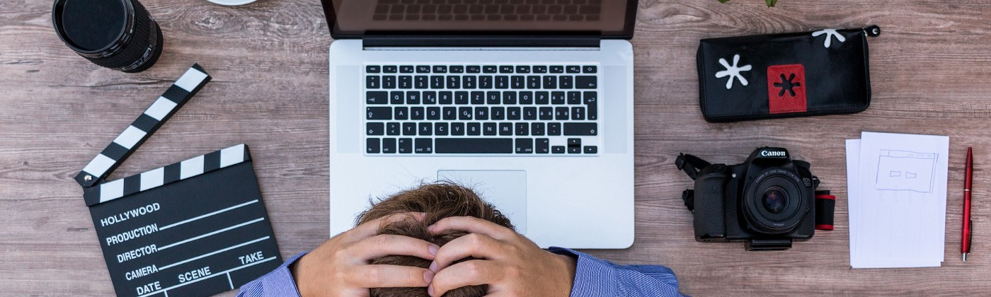 Writer bows over a laptop with hands clasped at the back of their head