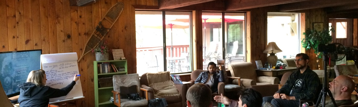 Offline Camp participants having a discussion in the living room of the Protocol Labs lodge while one of them takes notes.