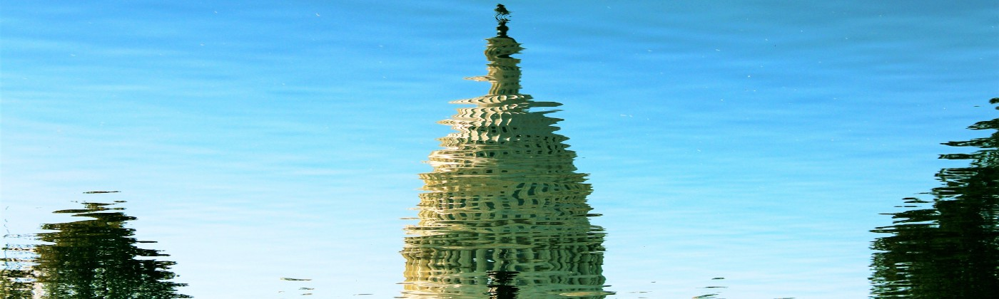 Reflection of Capitol Building against a blue reflected sky.