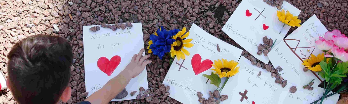 A child leaves a memorial card outside the El Paso Walmart