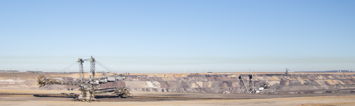 An open pit brown coal mine in Western Germany, with heavy machinery a cloud of pollution hanging over it