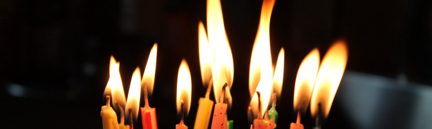 Image of about a dozen lit birthday candles.