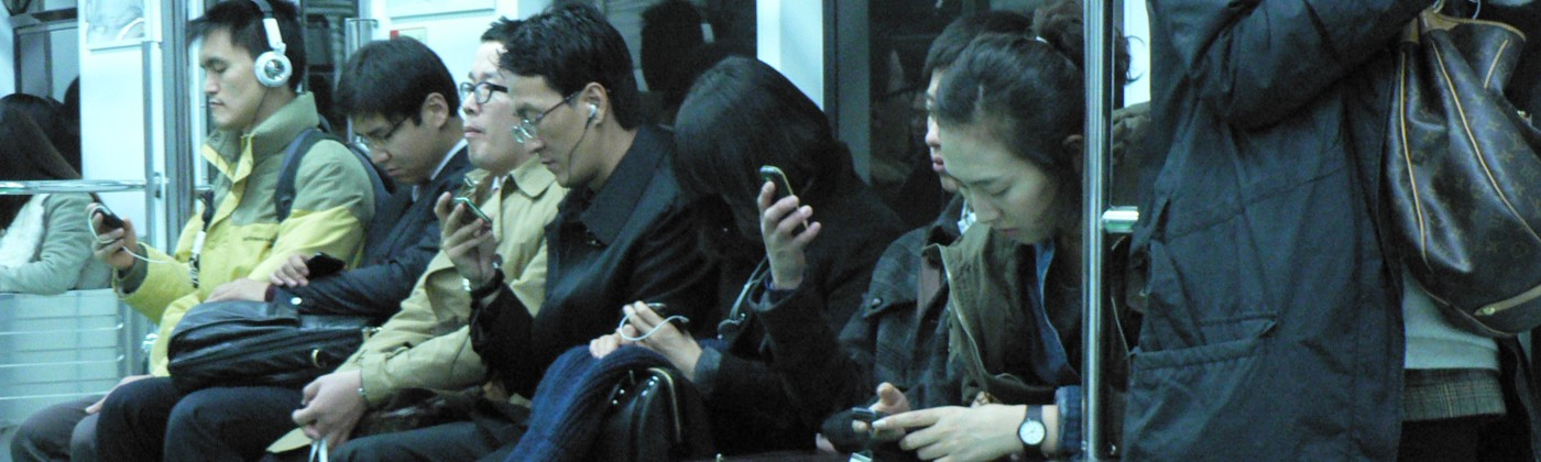 A group of Asians on a subway train, all staring at electronic devices