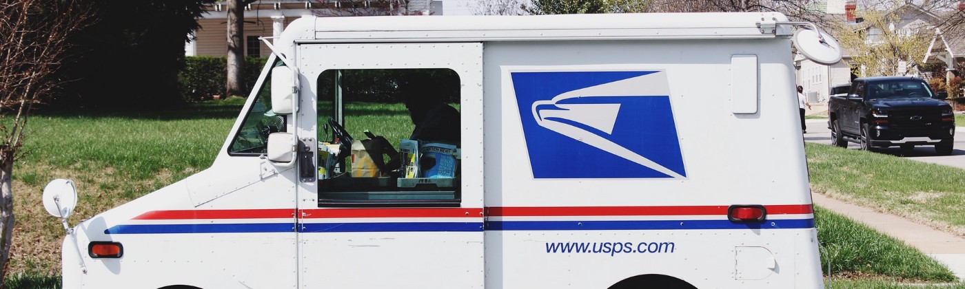 A US Postal Service truck parked on the curb in a residential neighborhood.
