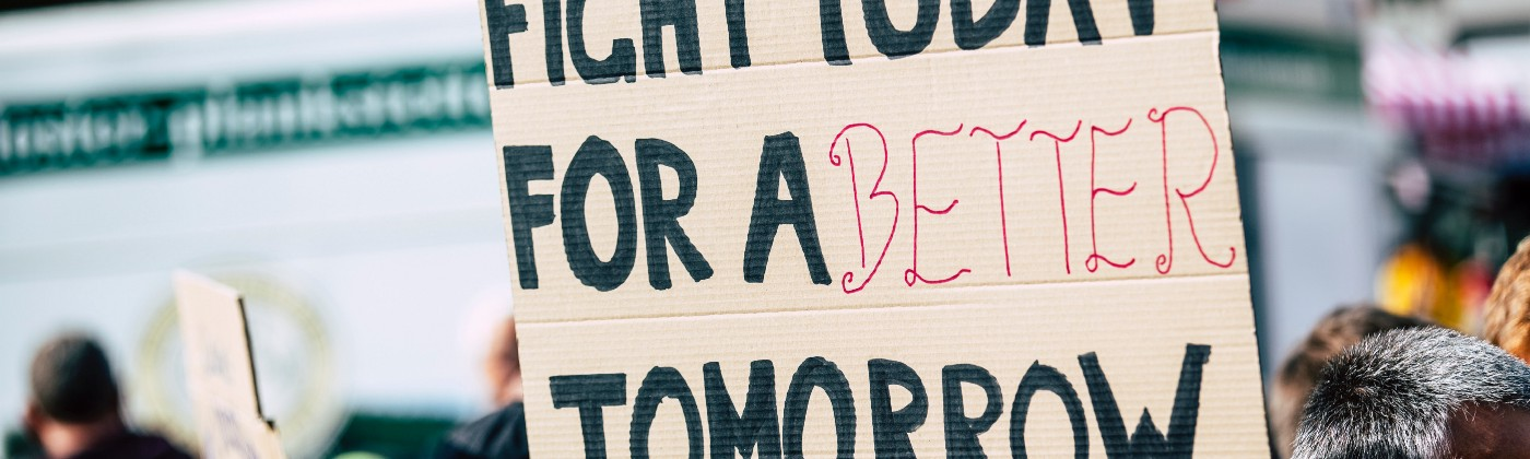 A person holds up a hand-written sign at a demonstration, which reads 'Fight Today For A Better Tomorrow'
