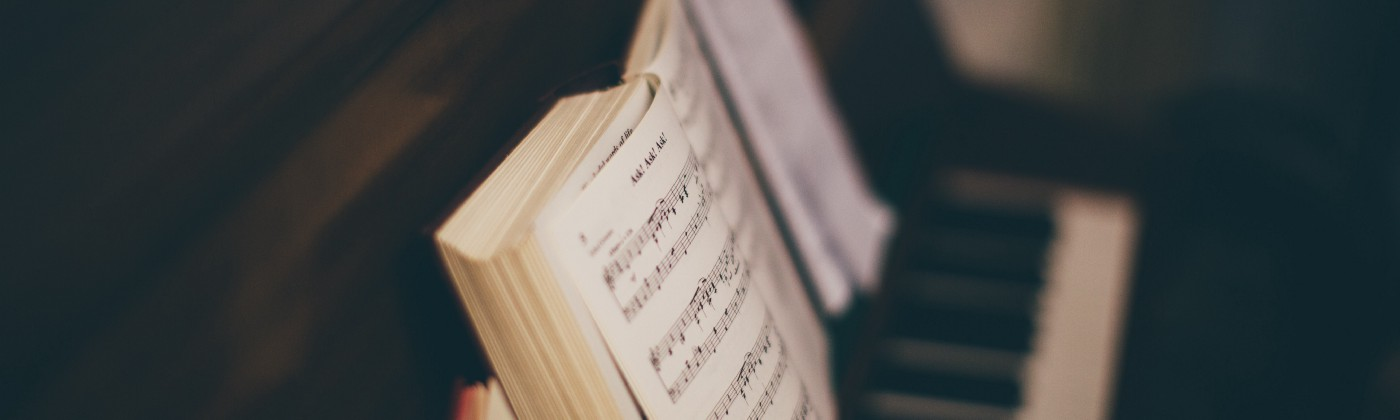 Opened music book on top of a piano