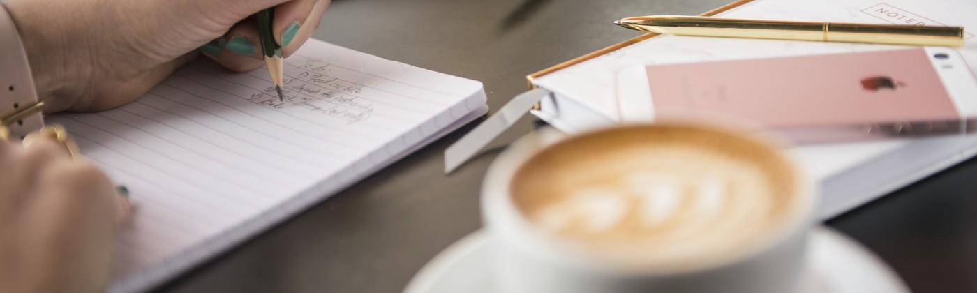 A hand writing in a notebook, with a latte in the foreground.