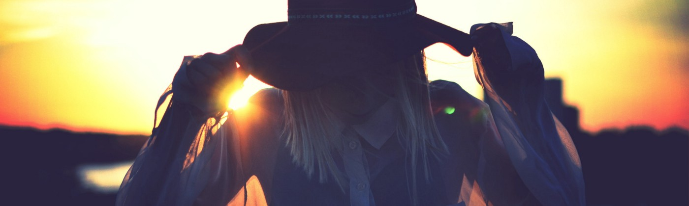 Woman with hat covering her face in front of sunset