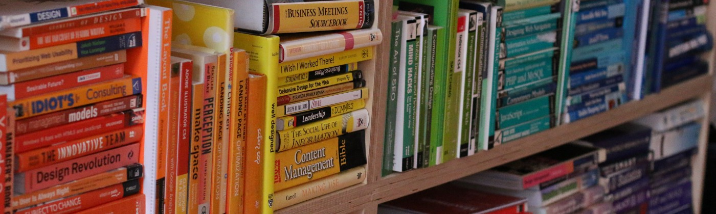 A bookcase of UX design books organised by colour