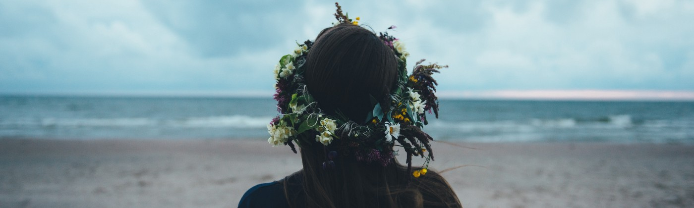 Woman with flowers in her long dark hair standing on a beach, facing away from the camera, looking out to the water