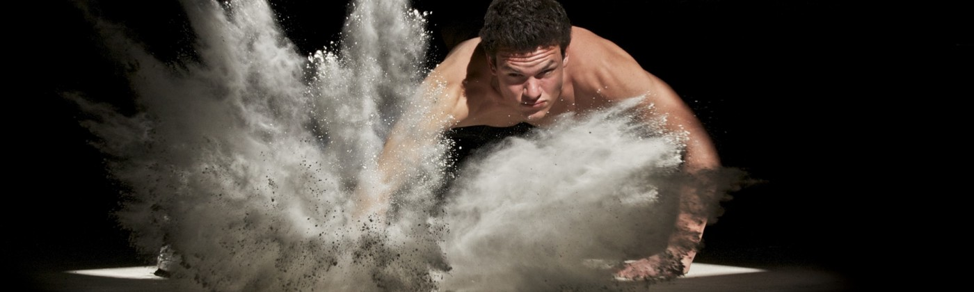 Strong, masculine man hitting the ground, creating a small explosion of dust.
