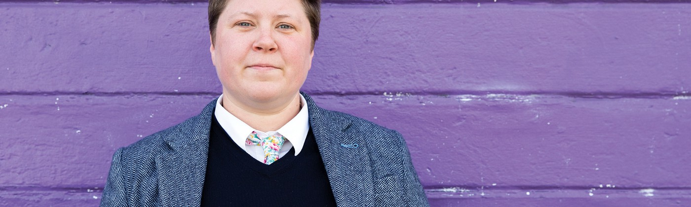 Carrie Bishop standing in front of a purple wall wearing a shirt, jacket and colourful tie