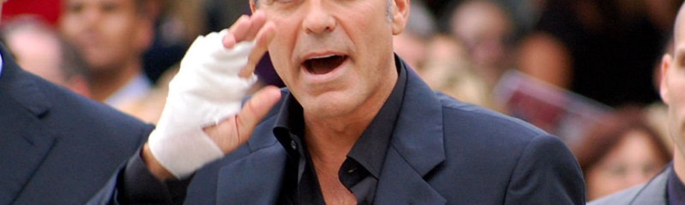 The real George Clooney attempting to call someone as he holds a bandaged hand to his face