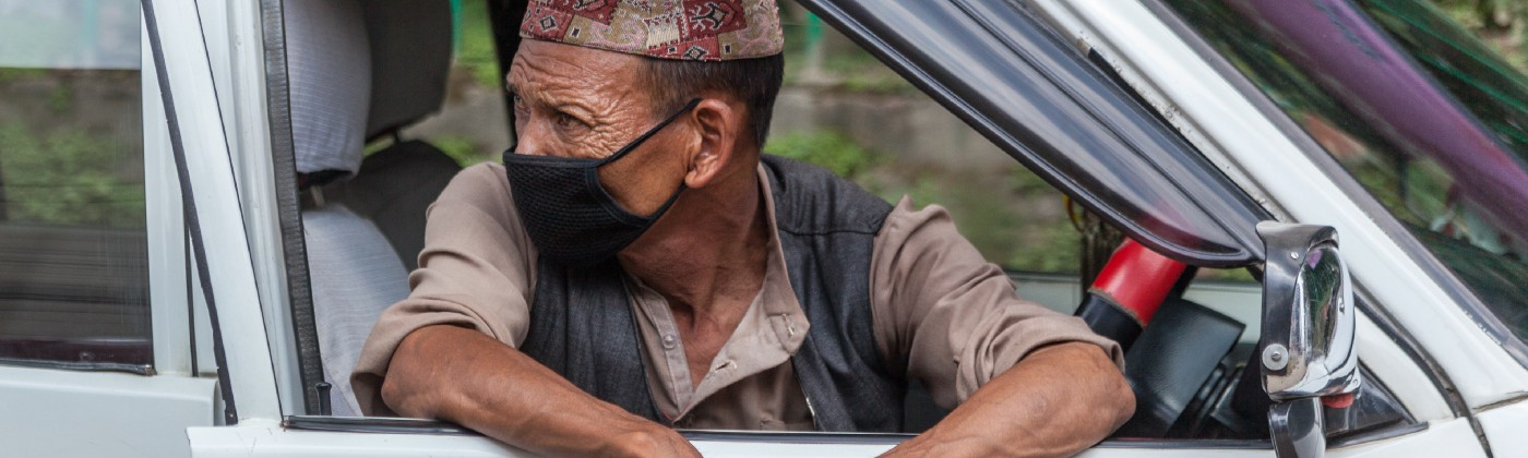 Taxi driver waiting for a fare wearing a face mask in Kathmandu, Nepal. Photo: © Mark Benham/Shutterstock