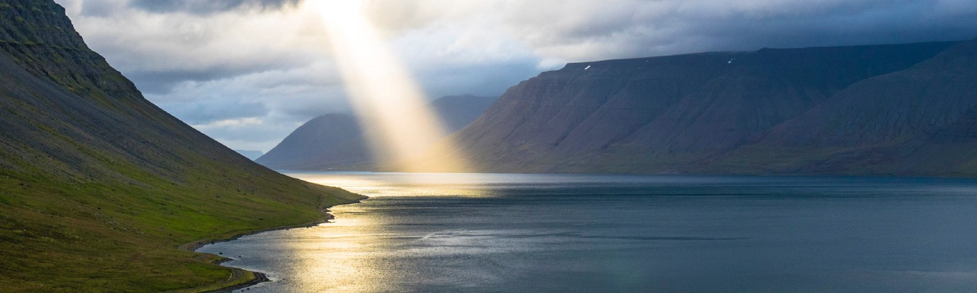 Sun piercing through the clouds and shining on a large body of water surrounded by green hills