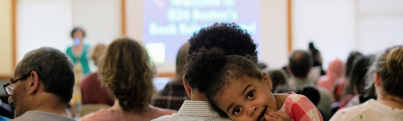 A toddler rests on her father's shoulder at an 826 Boston event.