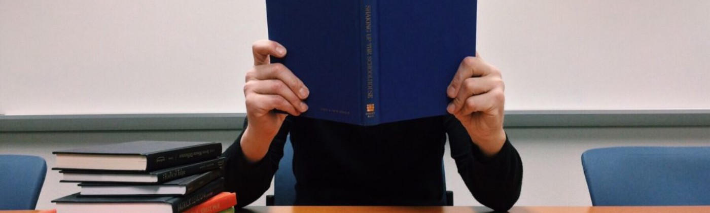 Guy holding up a book to his face with both hands, ironically, an unlikely studying pose, with a stack of books to his right