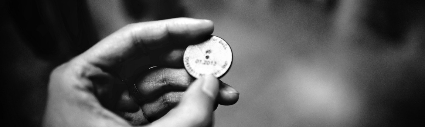 man holding a coin, this is to define the notion of holding virtual coins, in this case the HUNT token which the erc-20 token