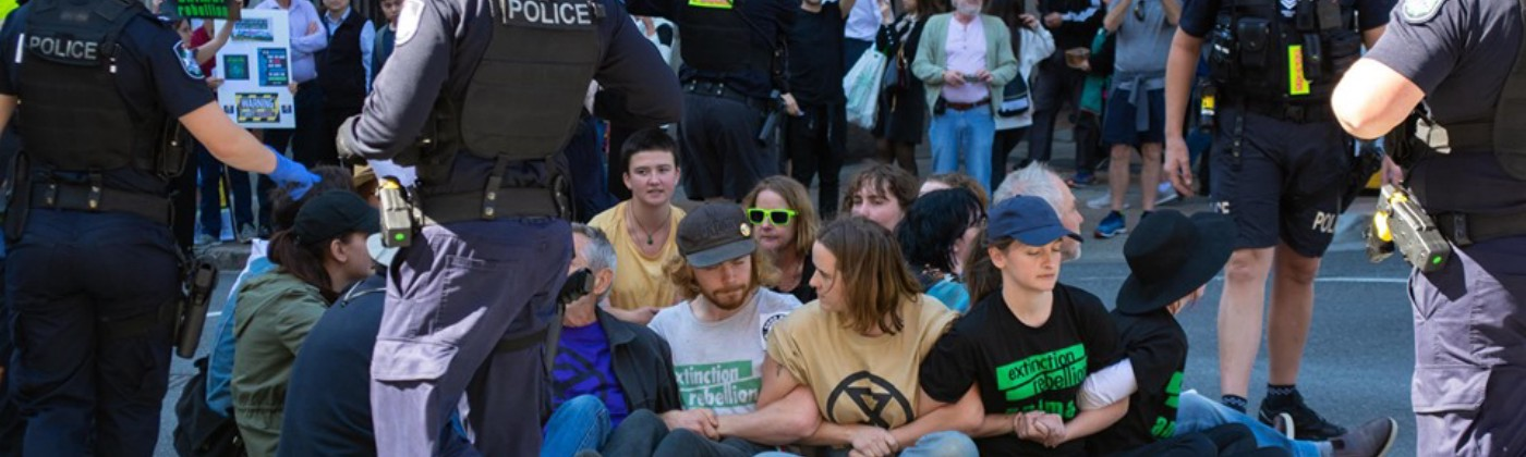 Extinction Rebellion protesters sitting in a circle with linked arms
