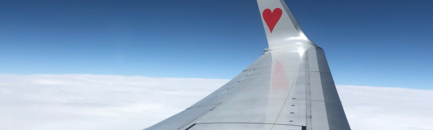 A plane soaring in the sky with a tiny heart on the end of its wing.