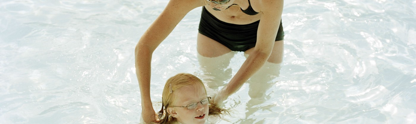 A mother teaching her daughter to swim.