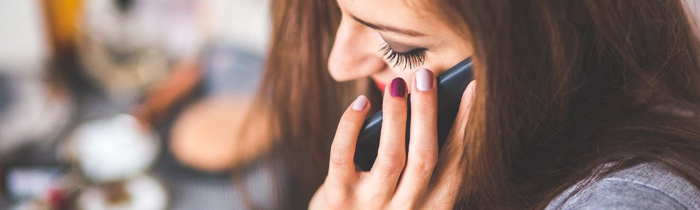 smiling woman with her friend talking on the phone about what she wants in her life that's better than what she has now