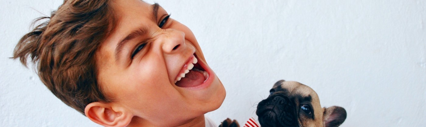 child holding a dog in a bow-tie, laughing maniacally