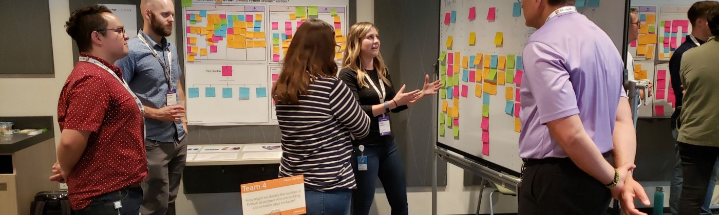 A woman presenting her group's Journey Map to a guest attending the leadership review on the final day of the workshop