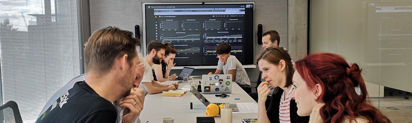 The engineering team working together to resolve a pratice incident with a dashboard of graphs in the background.