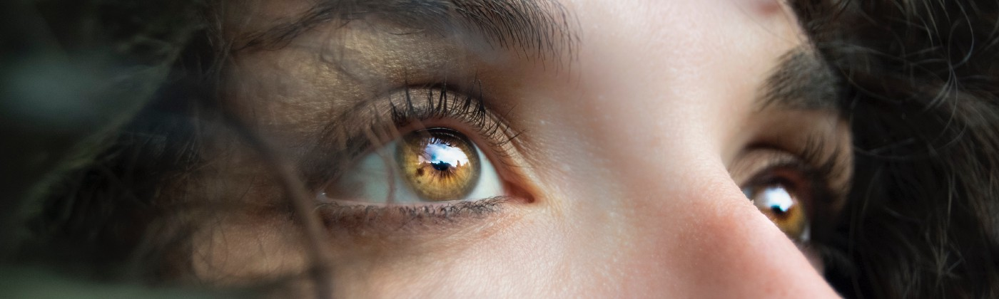 Close up of woman with light brown eyes, looking upward.