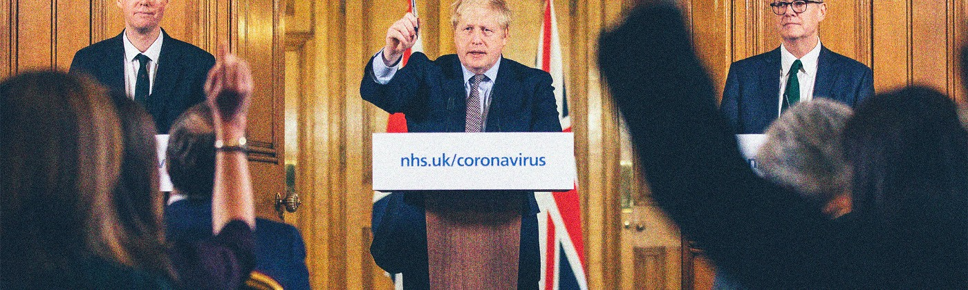 "Boris Johnson standing behind a podium for a live press briefing. The podium placard reads ""nhs.uk/coronavirus"" in blue text."