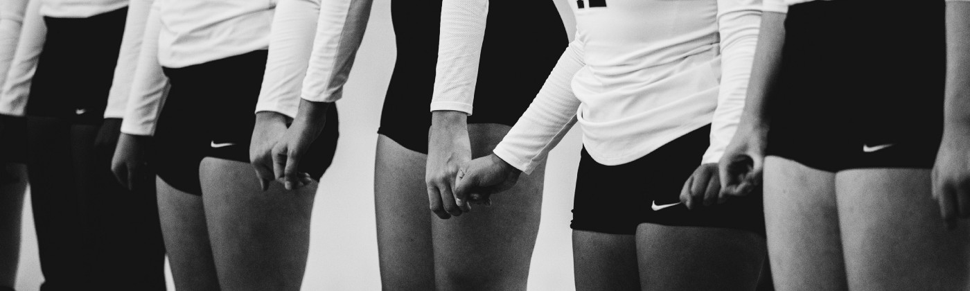Gray scale photography of women volleyball team lined up together.