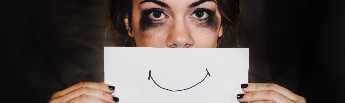 Woman masking sadness with a smile