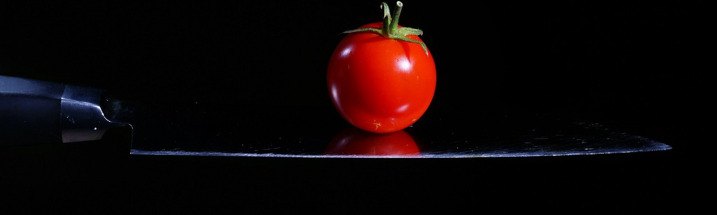 A red tomato balanced on the blade of a sharp knife